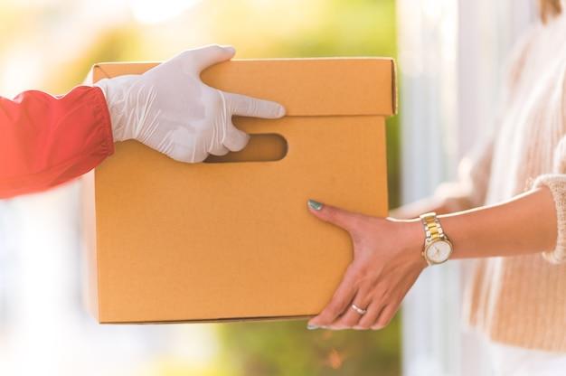 自宅で若い女性に箱を与える配達人、宅配便のコンセプト