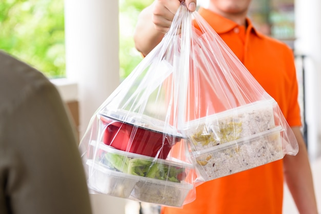 Delivery man giving lunch box meal in the bags to cutomer that ordered online at home