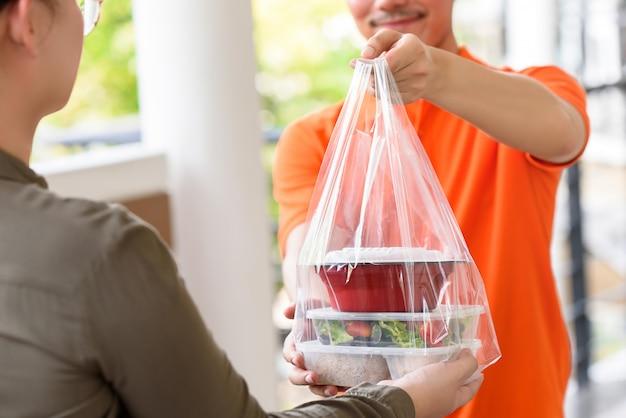 Доставка человек дает ланч-бокс еду в сумке к клиенту, который заказал онлайн дома