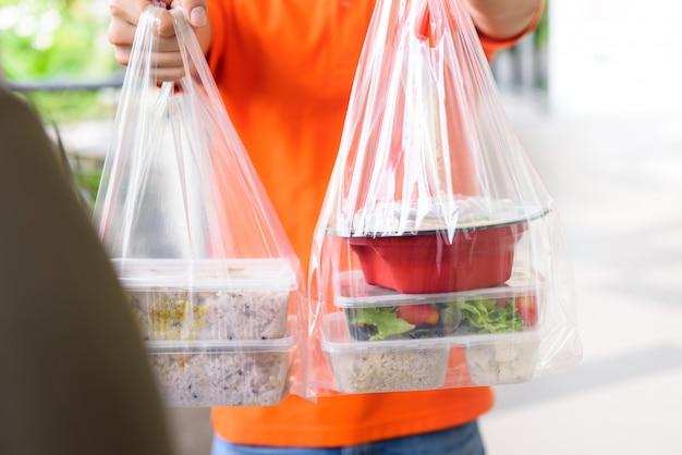 Доставка человек дает ланч-бокс еду в пакетах к клиенту, который заказал онлайн на дому