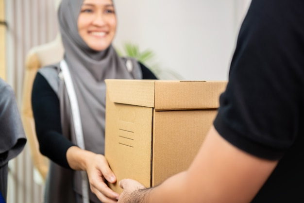 Delivery man giving parcel box to muslim woman at her shop