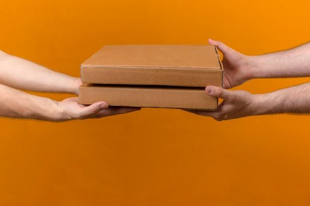 Uomo di consegna che dà le scatole per pizza al cliente sulla vista laterale arancione isolata