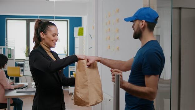 스타트업 기업에서 일하는 여성 사업가에게 음식 주문과 함께 테이크아웃 패키지를 제공하는 배달원