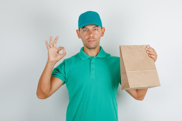 Delivery man in green t-shirt and cap doing ok sign with paper bag