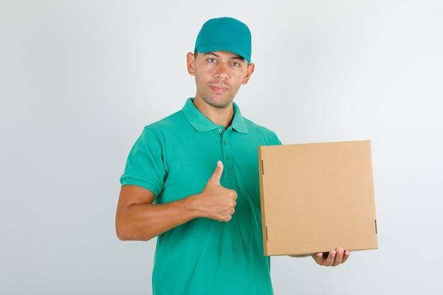 Delivery man in green t-shirt and cap holding box and showing thumb up