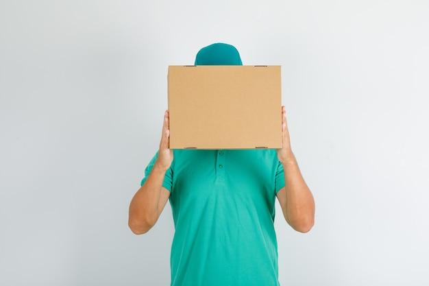 Fattorino in maglietta verde e cappuccio che tiene la scatola di cartone sul viso