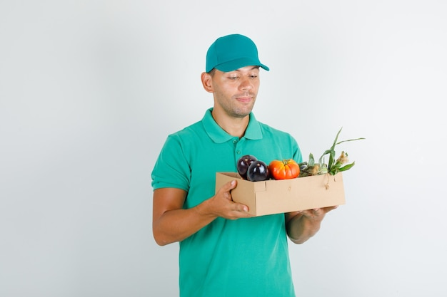 Delivery man in green t-shirt and cap holding vegetables in box and looking cheerful