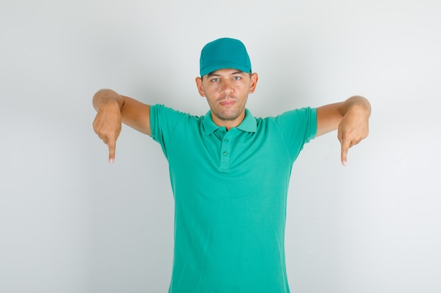 Delivery man in green t-shirt and cap pointing down and looking confident