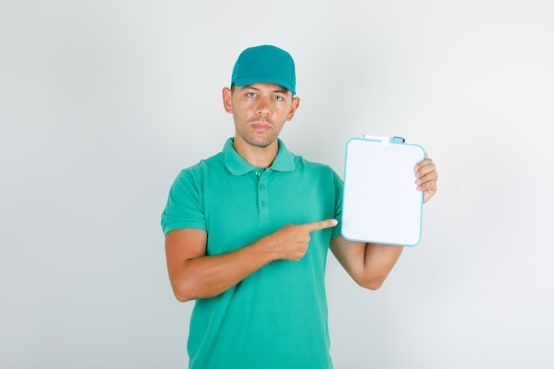 Delivery man in green t-shirt and cap pointing finger at board