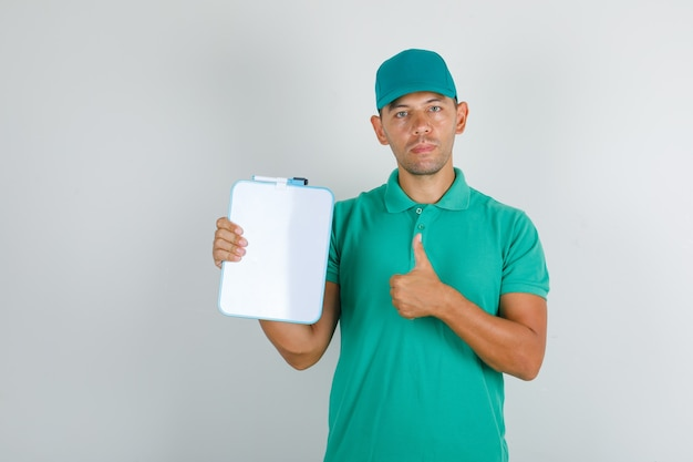 Delivery man in green t-shirt and cap showing thumb up with board