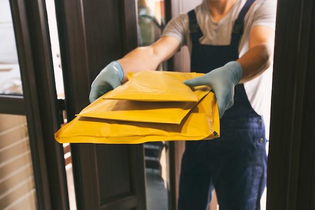 自宅でお客様に小包を渡す配達員