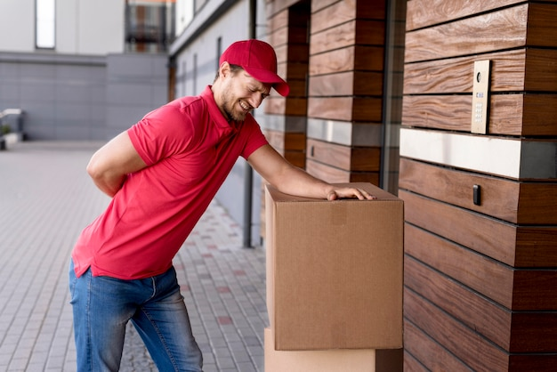 Delivery man having back pain from carrying