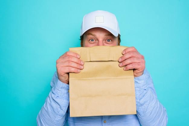 배달 남자는 음식 패키지와 함께 그의 얼굴을 숨 깁니다.