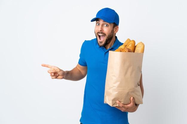 Доставщик, держащий сумку с хлебом, изолированную на белой стене, удивлен и показывает пальцем в сторону