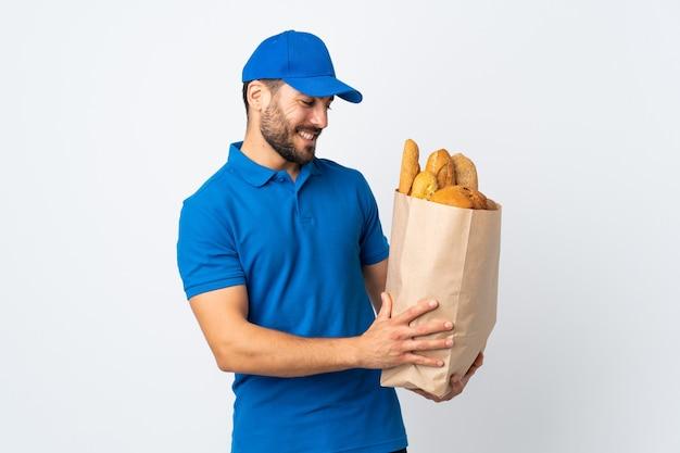 Доставщик с счастливым выражением лица держит сумку, полную хлеба