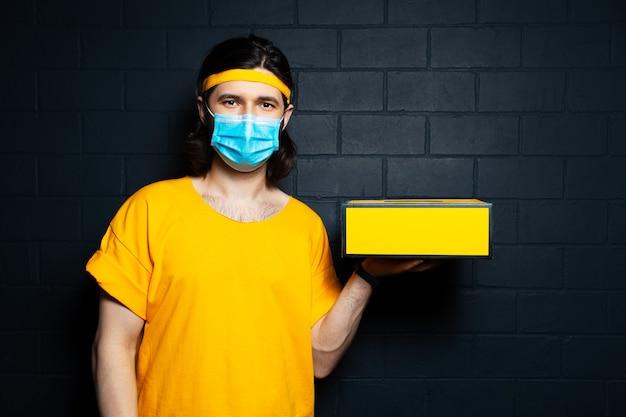 黒レンガの壁の背景に医療マスクと黄色のシャツを着た箱を保持している配達人。