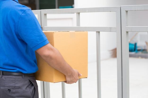 小包を持って、ドアの家で顧客を待っている配達人