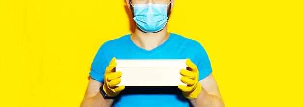 Доставка человек, держащий небольшую коробку. ношение медицинской маски для лица и защитных перчаток. желтый цвет.