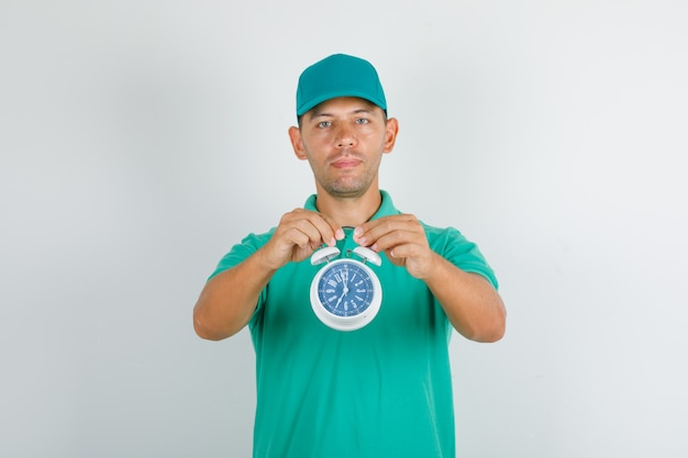 Delivery man holding alarm clock in green t-shirt and cap and looking positive