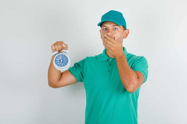 Delivery man holding alarm clock in green t-shirt and cap and looking worried