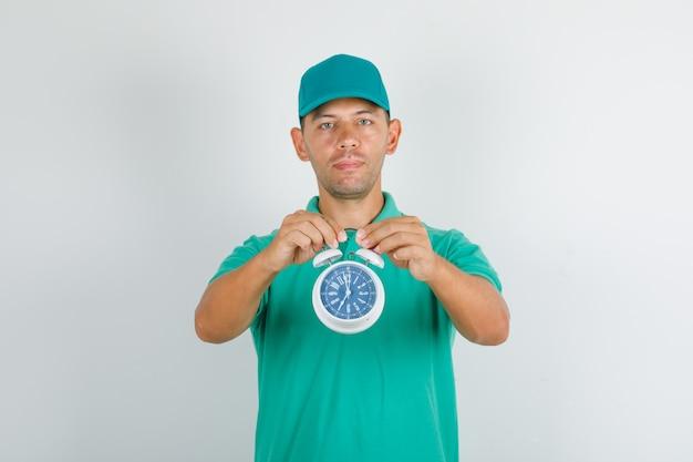 Доставщик держит будильник в зеленой футболке и кепке и выглядит позитивно