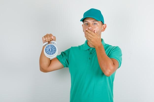 Доставщик держит будильник в зеленой футболке и кепке и выглядит обеспокоенным