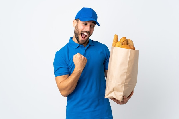 Delivery man holding a bag full of breads isolated on white celebrating a victory