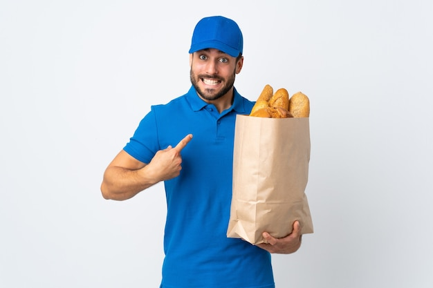 Delivery man holding a bag full of breads isolated on white wall with surprise facial expression