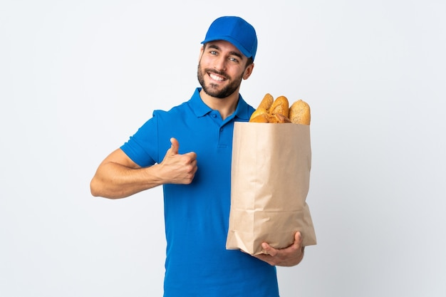 Delivery man holding a bag full of breads isolated on white with thumbs up because something good has happened
