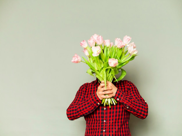 A delivery man holding a beautiful bouquet isolated on grey
