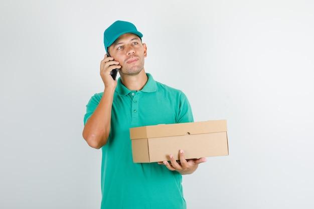 Доставщик держит коробку и разговаривает по телефону в зеленой футболке с кепкой