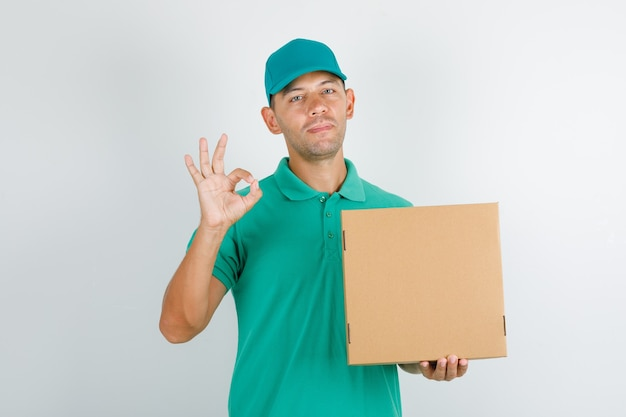 Delivery man holding box and doing ok sign in green t-shirt and cap