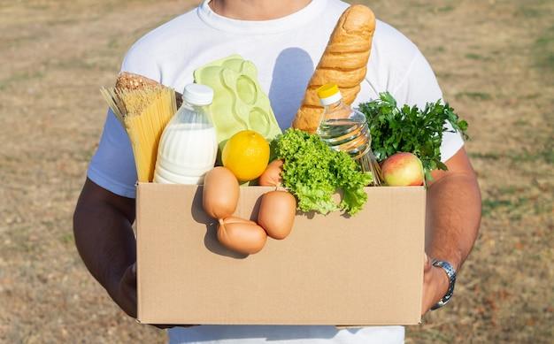 屋外で生鮮食品の食料品の箱を保持している配達人