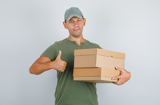 Delivery man holding boxes and showing thumb up in green t-shirt, cap. front view.