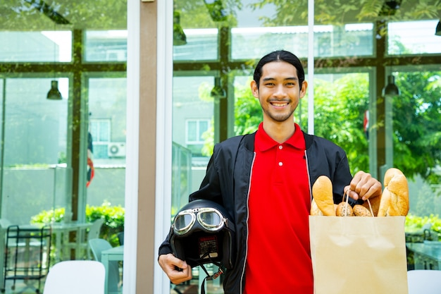 고객의 빵 음식 주문을 들고 배달 남자. 아시아 남자는 고객의 주문을 보여줍니다. 고객에게 주문을 준비합니다.