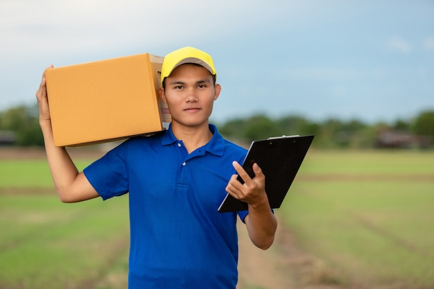 Delivery man holding brown parcel or cardboard boxes delivery to customer at countryside