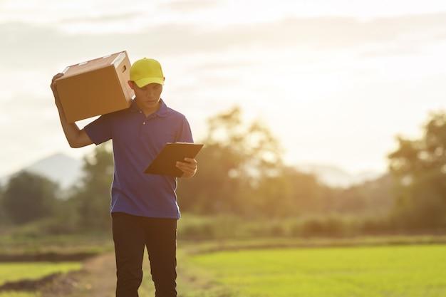 Доставка человек, держащий коричневые посылки или картонные коробки доставки до клиента в сельской местности