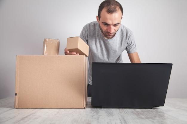 段ボール箱を持ってノートパソコンを使用している配達人。製品、コマース、小売、配送
