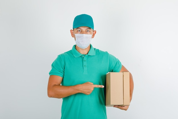 Delivery man holding cardboard box in green t-shirt with cap and mask
