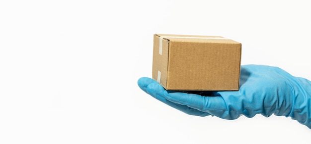 Доставка человек, держащий картонную коробку в резиновых перчатках