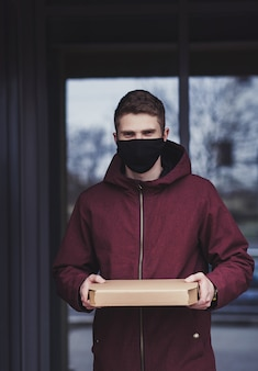 Delivery man holding cardboard box in mask