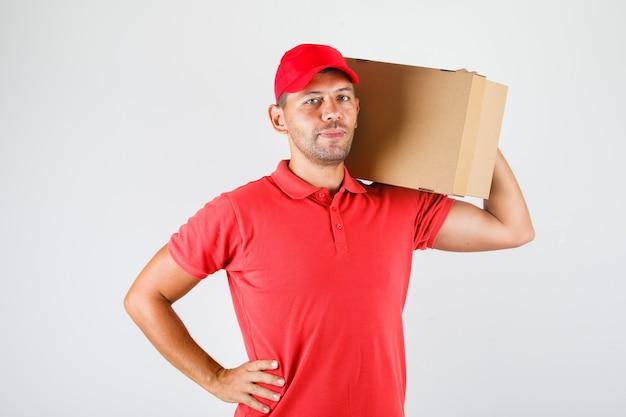 Курьер держит картонную коробку на плече в красной форме и выглядит позитивно