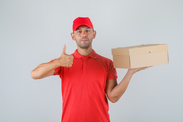 Delivery man holding cardboard box and showing thumb up in red uniform and looking positive.