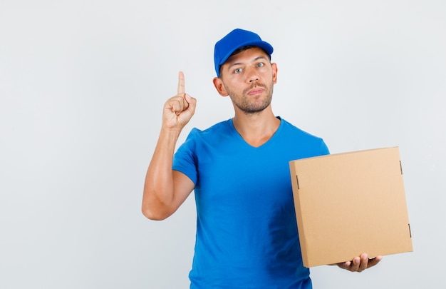 Delivery man holding cardboard box with finger up in blue t-shirt