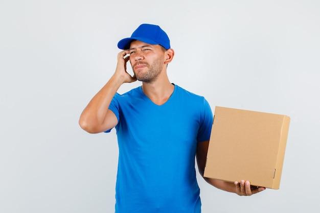 Uomo di consegna che tiene la scatola di cartone con le dita sul viso in maglietta blu