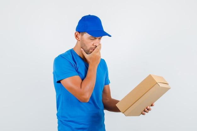Uomo di consegna che tiene la scatola di cartone con la mano sulla bocca in maglietta blu
