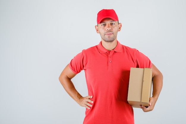 Uomo di consegna che tiene la scatola di cartone con la mano sulla vita in uniforme rossa, vista frontale.