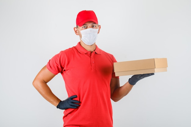 Uomo di consegna che tiene la scatola di cartone con la mano sulla vita in uniforme rossa, mascherina medica, vista frontale dei guanti.