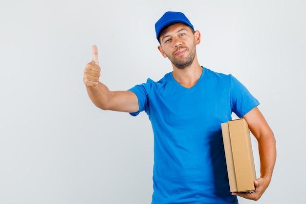 Uomo di consegna che tiene la scatola di cartone con il pollice in su in maglietta blu