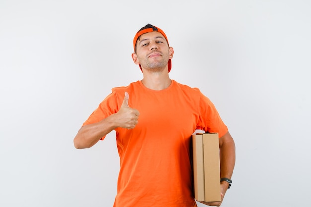 Delivery man holding cardboard box with thumb up in orange t-shirt and cap and looking confident